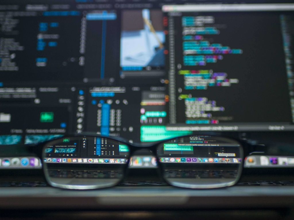 Close up looking in to a pair of glasses to screens with codes. Enable Education helped fight cyber crime with cyber security policy training.