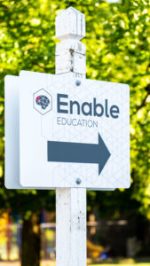 Signage for the walkway to Enable Education, arrow pointing right