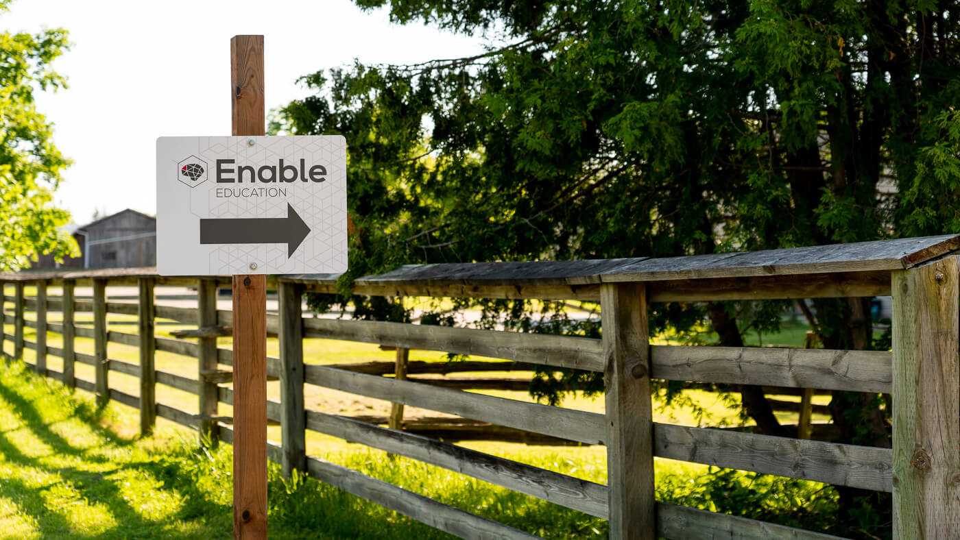 Signage for the entrance to Enable Education, arrow pointing right.