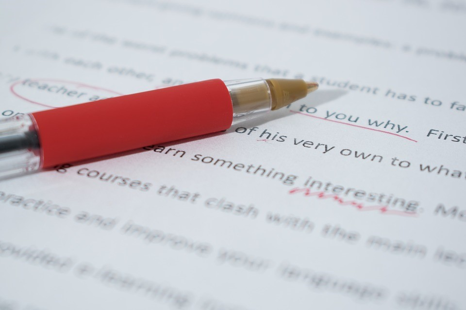 A red pen editing printed text