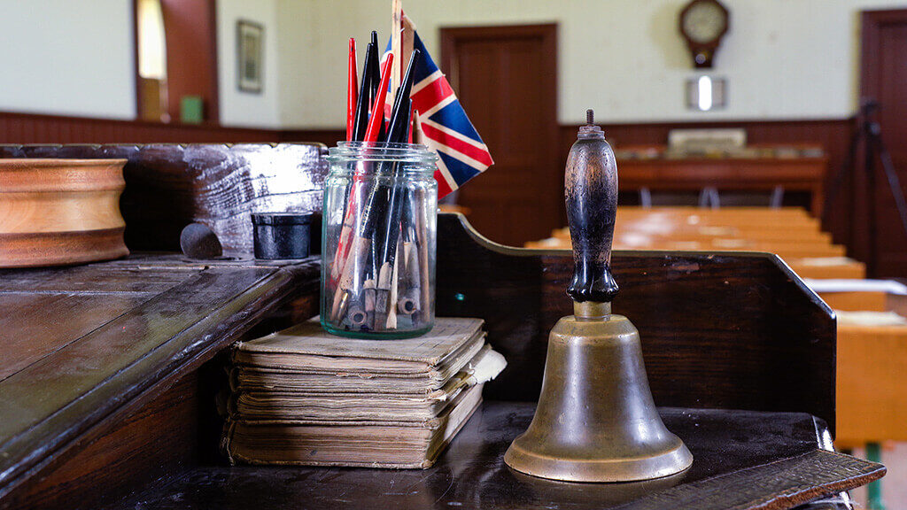 Union Jack flag, brass bell, and other items on teachers desk in schoolhouse at Country Heritage Park