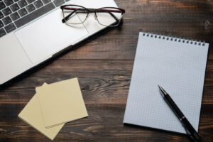 Laptop with glasses on it, a notebook with a pen, and notes on a dark wooden table. Close up for your text, top view