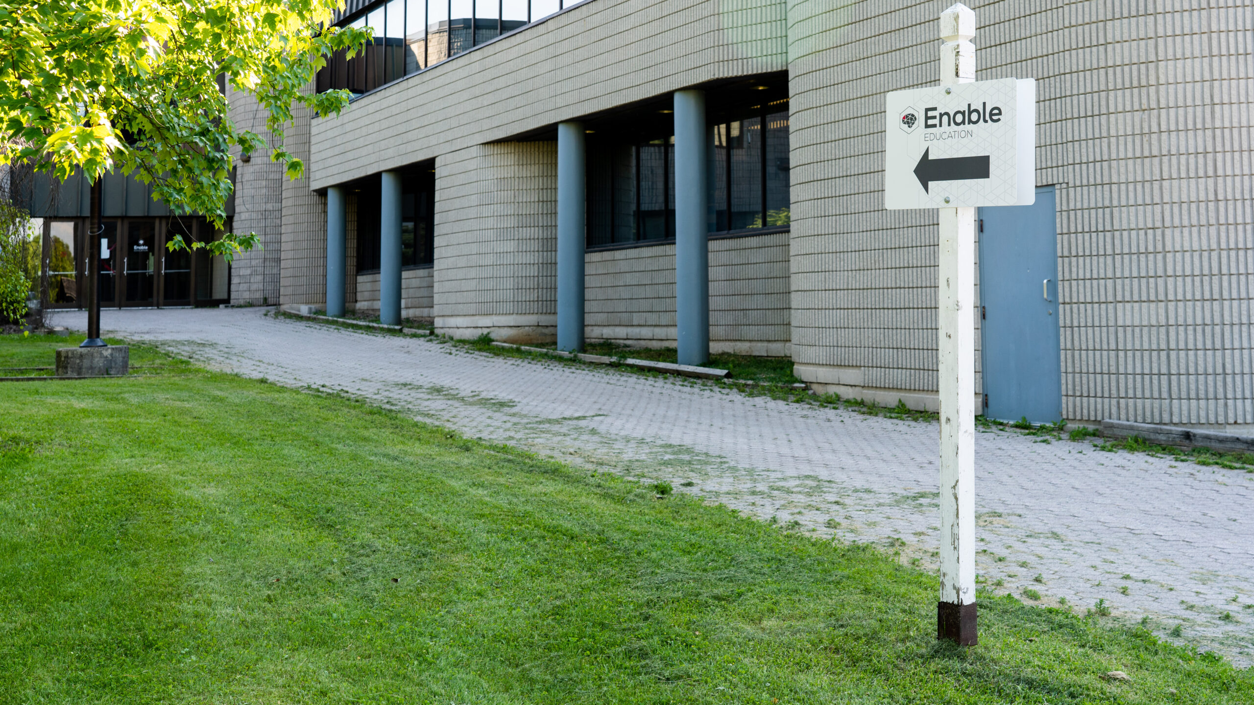 Enable Education is located on the second floor inside the grey building.