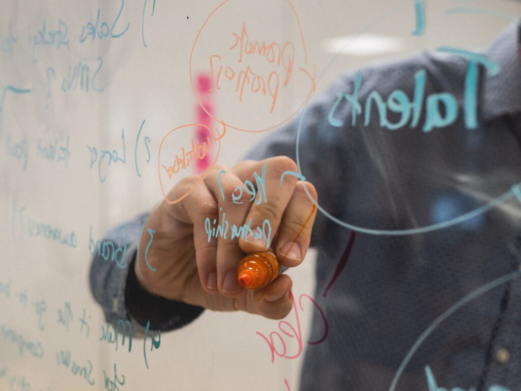 Man writing solutions in coloured marker on a glass board